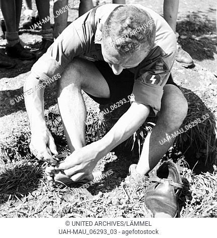 Ein Hitlerjunge im Hitlerjugend Lager bei der Fußpflege als Vorbereitung zum Marsch, Österreich 1930er Jahre. A Hitler youth taking care for his feet as...
