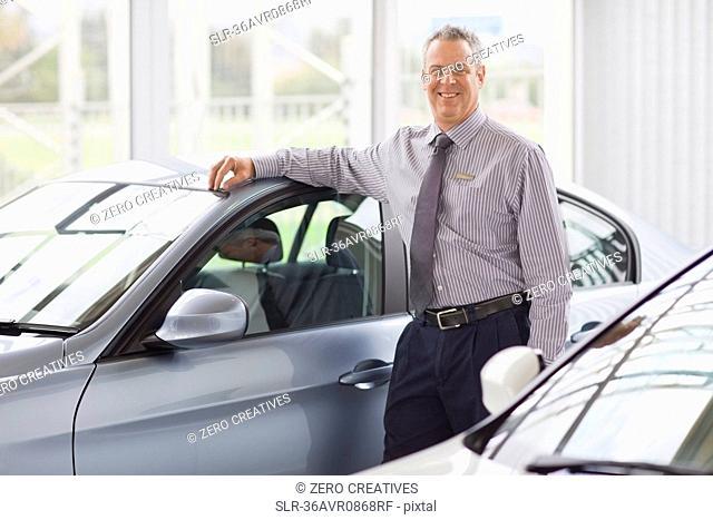Salesman standing by car in showroom