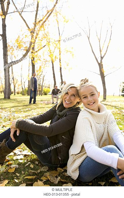Portrait smiling mother and daughter sitting back to back in sunny autumn park