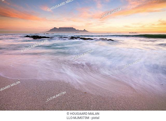 Surf on beach at Table Bay, with Table Mountain in background at sunset, Bloubergstrand, Western Cape Province, South Africa