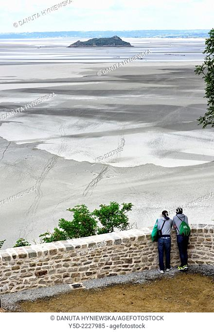 tourists looking to bay of Mont Saint-Michel at low tide, Tombelaine islet in the background, view from Mont Saint-Michel monastery, Normandy, France