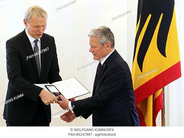 German Federal President Joachim Gauck (R) awards the Federal Cross of Merit to Ulrich Wessel from Haltern am See at Bellevue Palace in Berlin, Germany