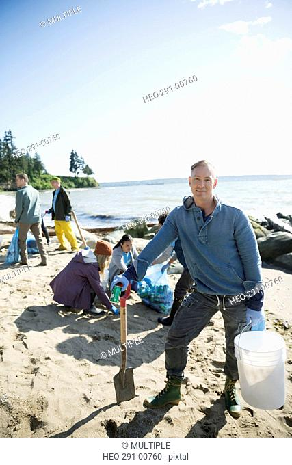 Portrait smiling beach cleanup volunteer picking up litter on sunny beach