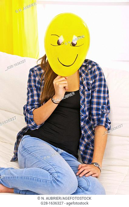 Young teenage girl holding and hiding behind a yellow balloon with a smiling face drawn on it