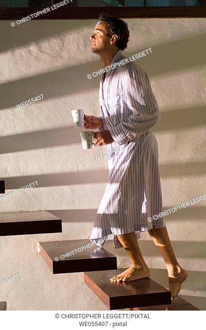 man in bathrobe stepping up stairs and holding mugs