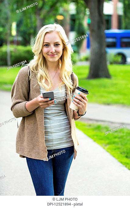 A beautiful young woman with long blond hair holding a coffee cup and texting on her smart phone while walking in a university campus; Edmonton, Alberta, Canada