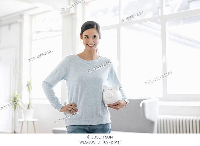 Young woman holding piggy bank under her arm