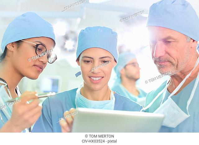 Surgeons using digital tablet in operating room