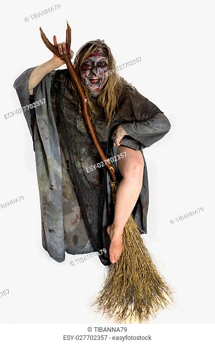 An ugly witch, erotically wraps her bare leg around a witches broom