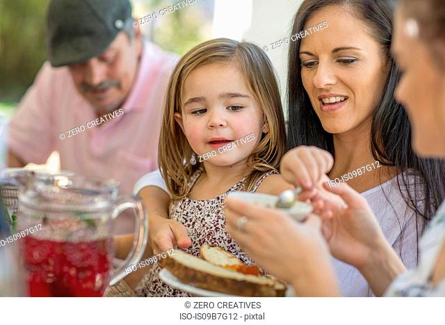 Girl having lunch with family outdoors