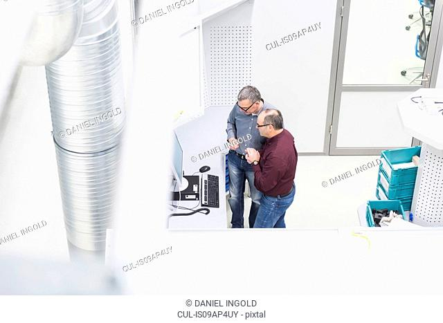 High angle view of manager and factory worker checking computer monitor