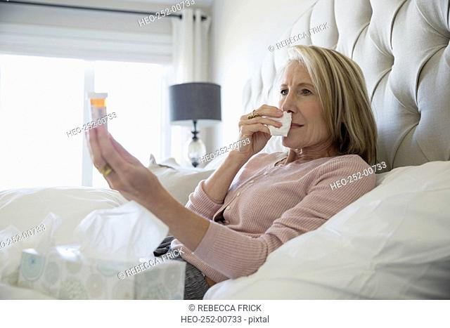 Sick woman with tissues prescription bottle in bed