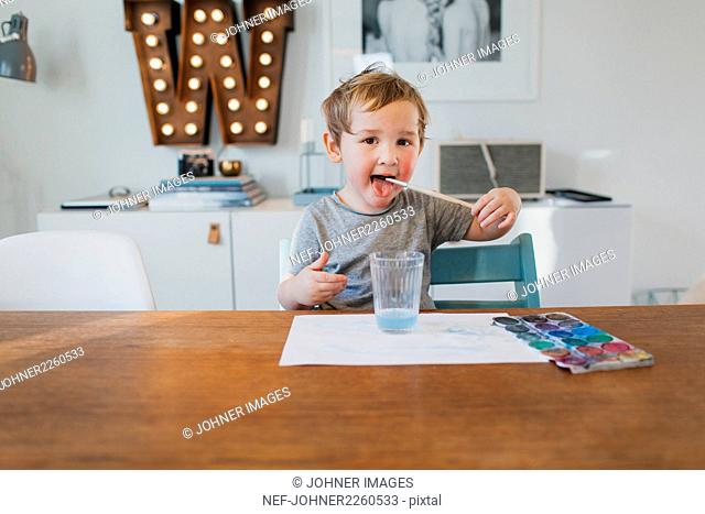 Boy putting paintbrush in his mouth