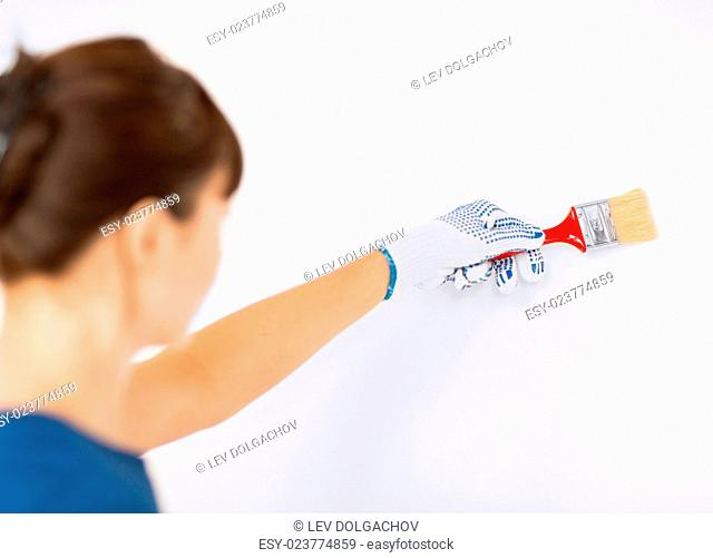 interior design and home renovation concept - woman with paintbrush colouring the wall