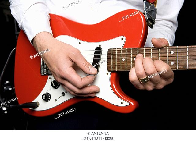 Detail of a man playing an electric guitar