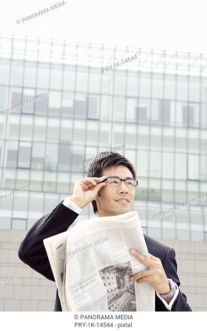 Business man standing, one hand adjusting glasses, the other holding sheets of newspaper