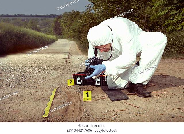 Crime scene investigation - photographing of car tire print left on crime scene