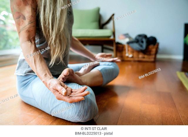 Caucasian woman meditating on floor