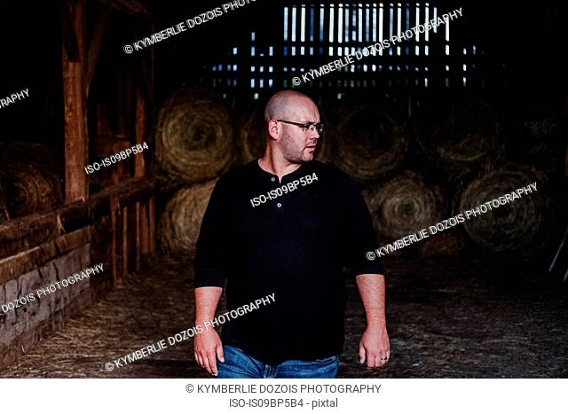 Man walking out of barn, hay bales in background