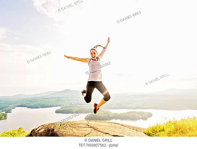 Young woman jumping over mountain top