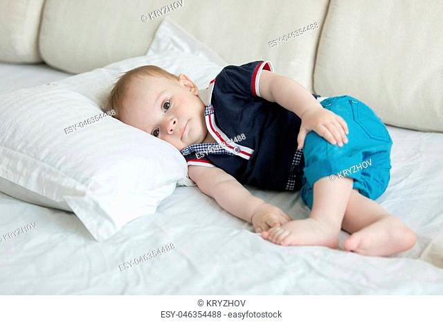 Cute baby boy lying on big white pillow on bed