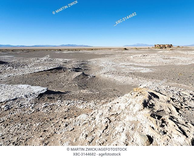 Ruins of buildings for salt processing. Landscape at the salt flats Salar Salinas Grandes in the Altiplano. South America, Argentina
