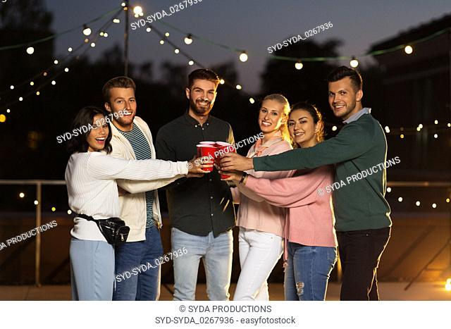 friends clinking party cups on rooftop at night