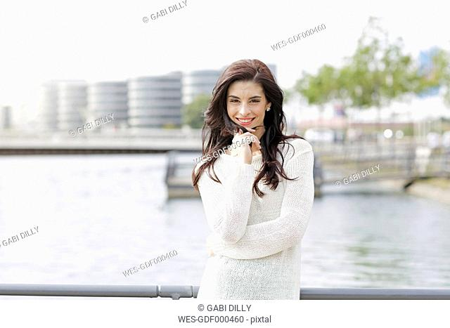 Germany, North Rhine-Westphalia, Duisburg, portrait of happy young woman standing in front of media harbour