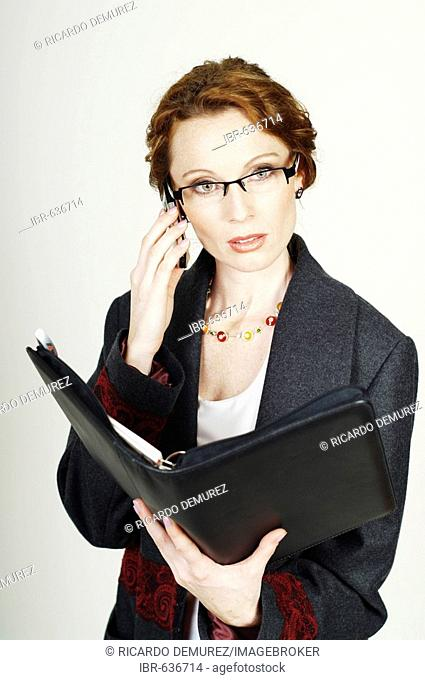 Businesswoman wearing eyeglasses making a call with her mobile phone
