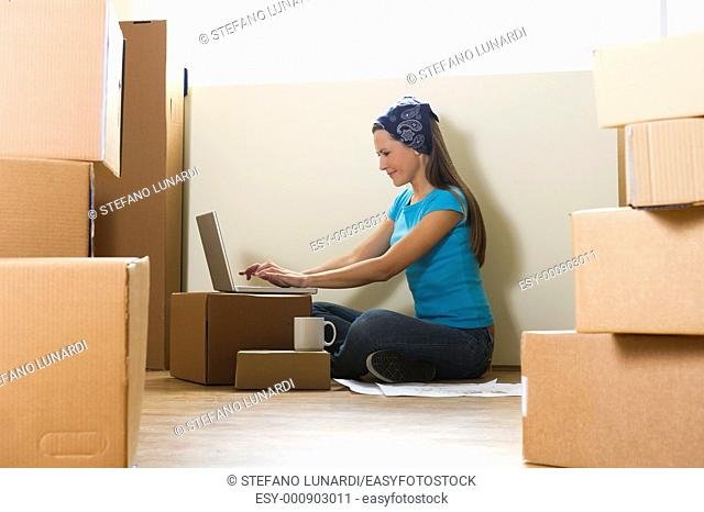 Woman with laptop in new home