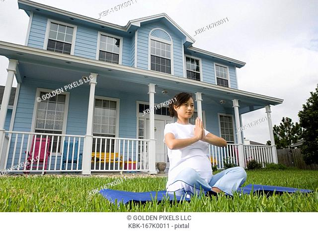 Pregnant woman in a yoga position in front of house