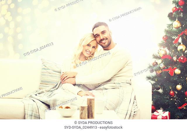 happy couple hugging over christmas tree