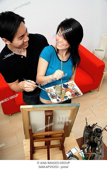 Couple in front of painting easel, looking at each other, high angle view