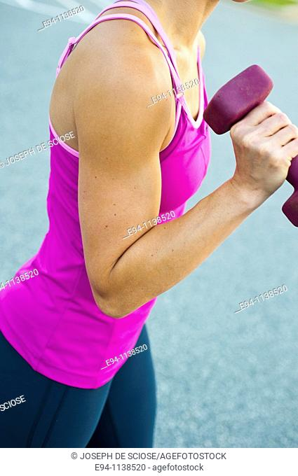 Close up of a thirty year old woman's flexed bi-cep pumping a dumbbell