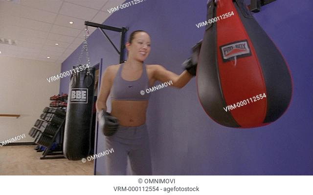 Excited woman punching and kicking punch bag