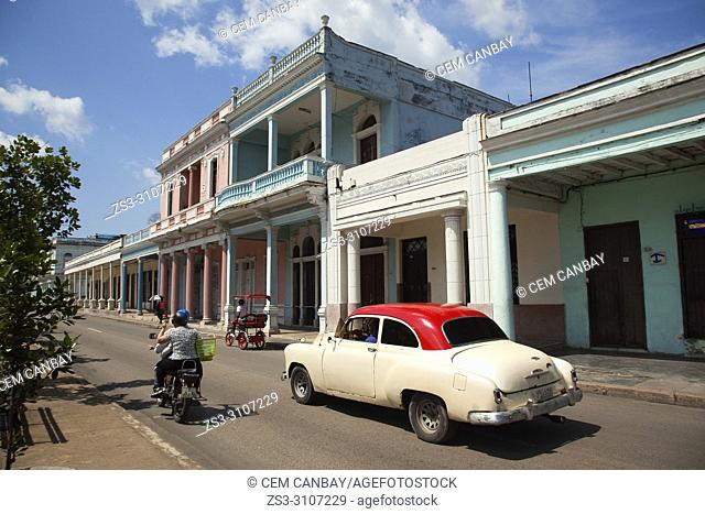 Old American car, motorcycle and bici taxi at Paseo Del Prado or so called Boulevard in the city center, Cienfuegos, Cuba, West Indies, Central America