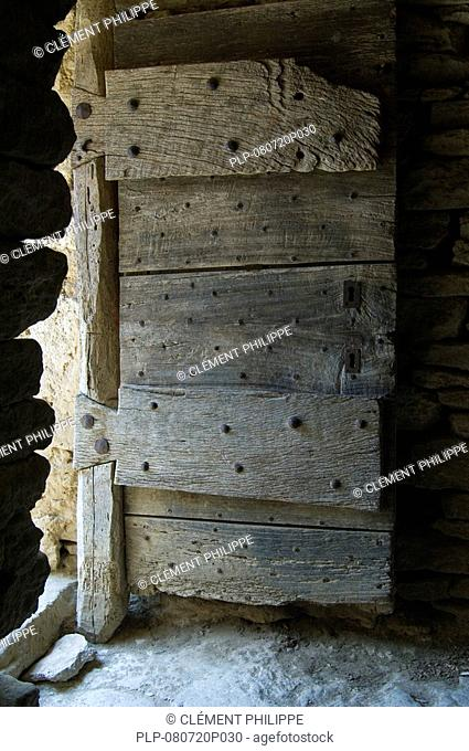 Old wooden door in the restored village Les Bories with its traditional stone Gallic huts, Gordes, Provence, France
