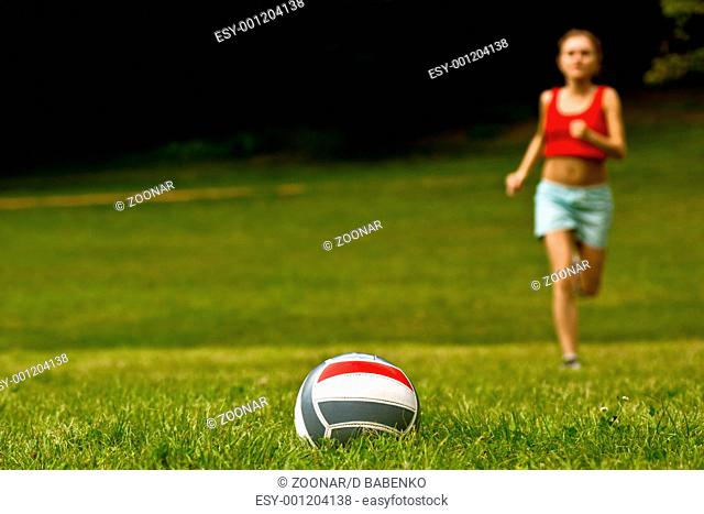 Girl run for volleyball ball lay on grass