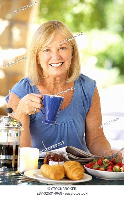 Senior woman eating breakfast outdoors