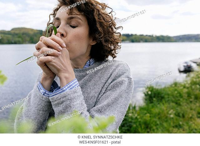Woman at lake blowing grass blade