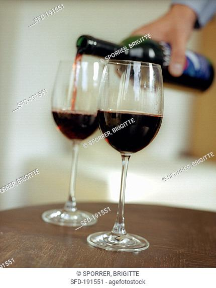 Pouring red wine into glasses (grainy effect)