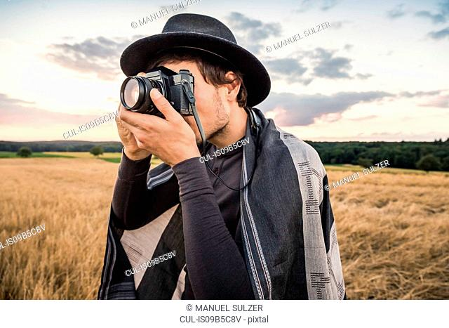 Mid adult man, standing in field, taking photograph with SLR camera, Neulingen, Baden-W³rttemberg, Germany