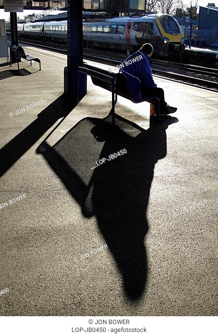 England, Oxfordshire, Oxford, A man in silhouette waiting for a train at Oxford Station