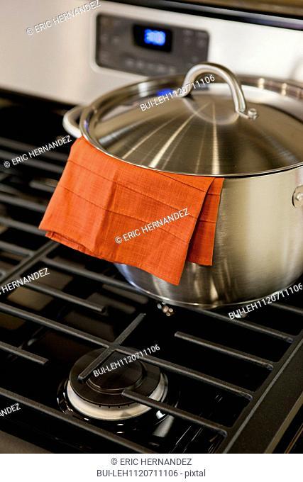 Orange cloth in saucepan on gas stove in kitchen; Azusa; California; USA