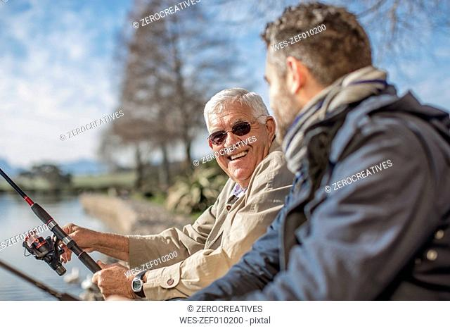 Senior man and adult son fishing together