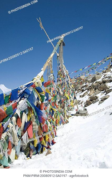 Prayer flags in a snow covered mountain, Khardung La, Ladakh, Jammu And Kashmir, India