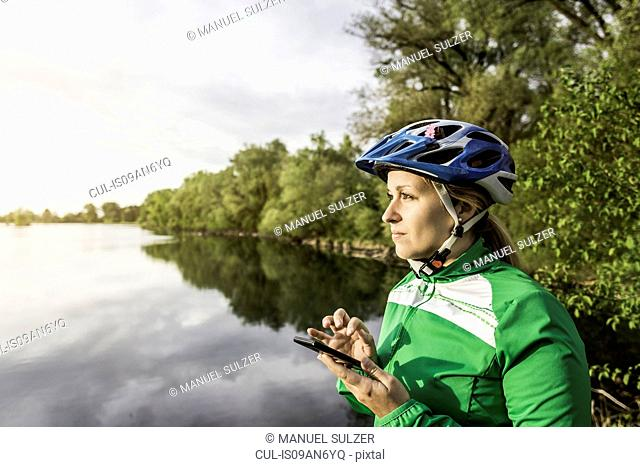 Young female at lake texting on smartphone, Augsburg, Bavaria, Germany