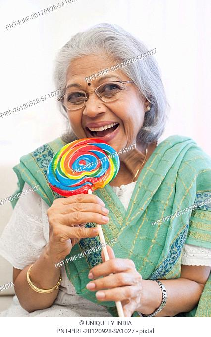 Senior woman eating a lollipop and smiling