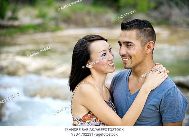 Young couple in love - man, 22, hispanic, woman, 20, korean, location natural environment near Leakey, Texas, USA