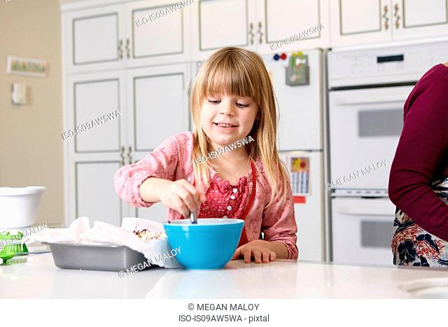 Girl mixing cake at kitchen counter